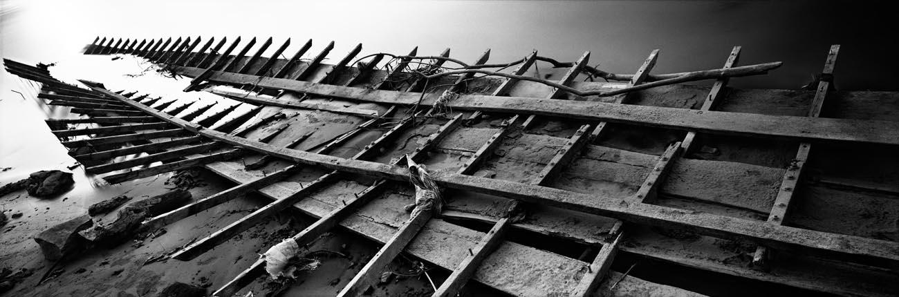 Zeng Nian,Carcasses de bateaux au bord du Mékong. Laos. Février 2010. Tirage jet d'encre sur papier INNOVA Exhibition Photo Baryta 310 gsm, 128.6X42.5cm / 04/15