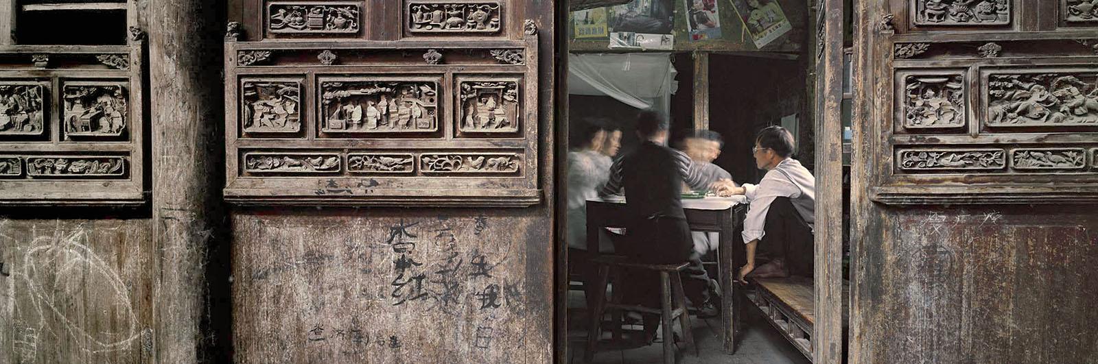 Zeng Nian, Village de Zhaji, jeu de mahjong, au premier plan: sculptures sur portes endommagées pendant la révolution culturelle, province de l'Anhui Chine. 2000. Tirage jet d'encre sur papier INNOVA Exhibition Photo Baryta 310 gsm, 128.6X42.5cm /01/15