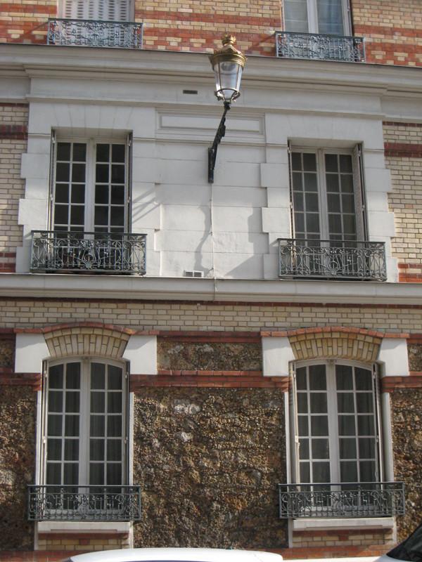 Détail de la façade de la construction originelle, montrant entre autres les travées centrales parées de pierre de taille.