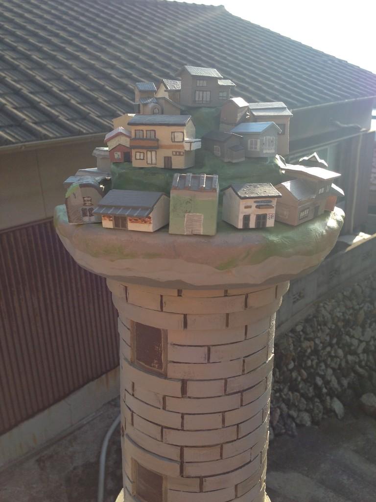 男木島の象徴である灯台と山のように連なる家並みのイメージを組み合わせた造形。