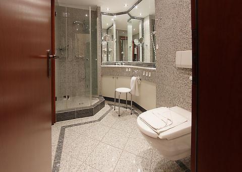 Granitgefliestes Duschbad mit Duschwand aus Glas, Föhn, Fußbodenheizung.