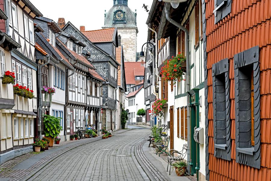 Bänke, Blumen, Pflanzkästen und Kübel schmücken Die Maurenstraße mit ihren gepflegten Fachwerkhäusern. Im Hintergrund ist der Turm der Wolfenbütteler Hauptkirche Beatae Mariae Virginis zu sehen.