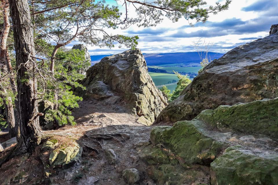 Zwischen zerklüfteten Felen hindurch sieht man ein weites Tal. Bäume stehen am Rand.