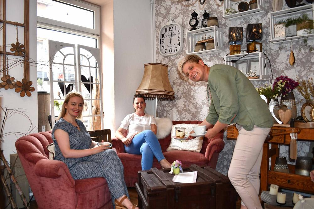 Eine Frau bedient zwei Gäste in einem Café in Wolfenbüttel. Die Gäste sitzen auf einem Sofa und einem Sessel. Im Hintergrund steht eine alte Lampe.