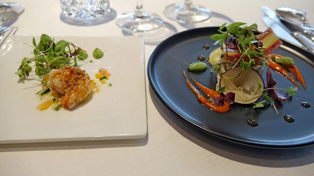 La première et la deuxième entrées « surprise » du Chef : Tourteau décortiqué, légumes croquants et espuma à la livèche - Queue de langoustine poêlée, crumble saté et houmous de petits pois