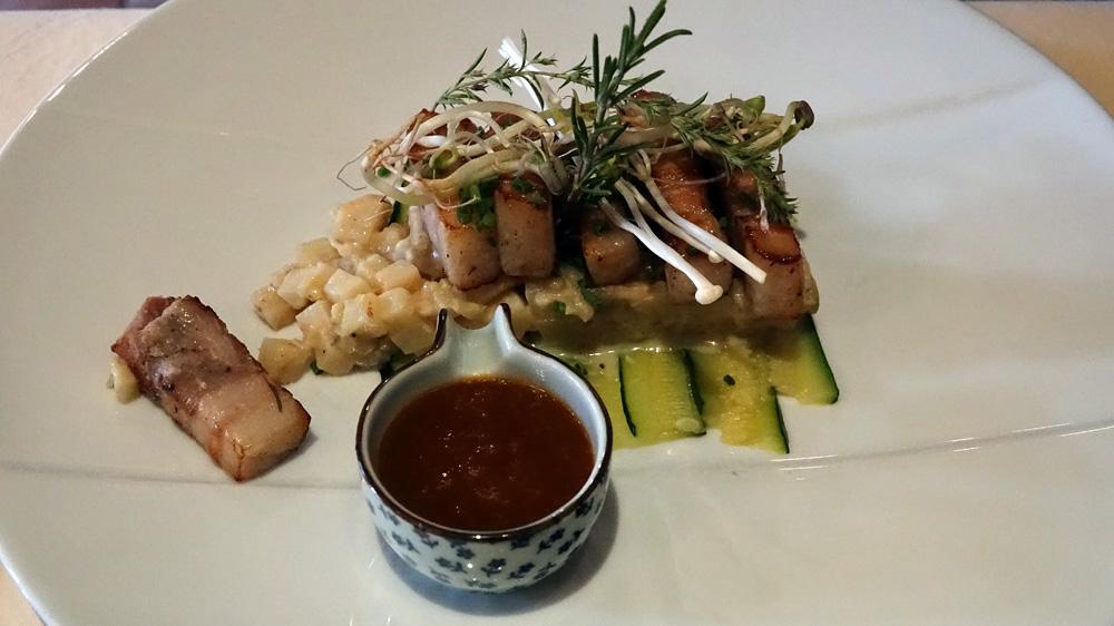 Poitrine de cochon de la ferme de la Beurrerie, rôtie, sur un lit de courgettes, risotto de céleri et aubergine, jus à la fleur de Macé des Indes