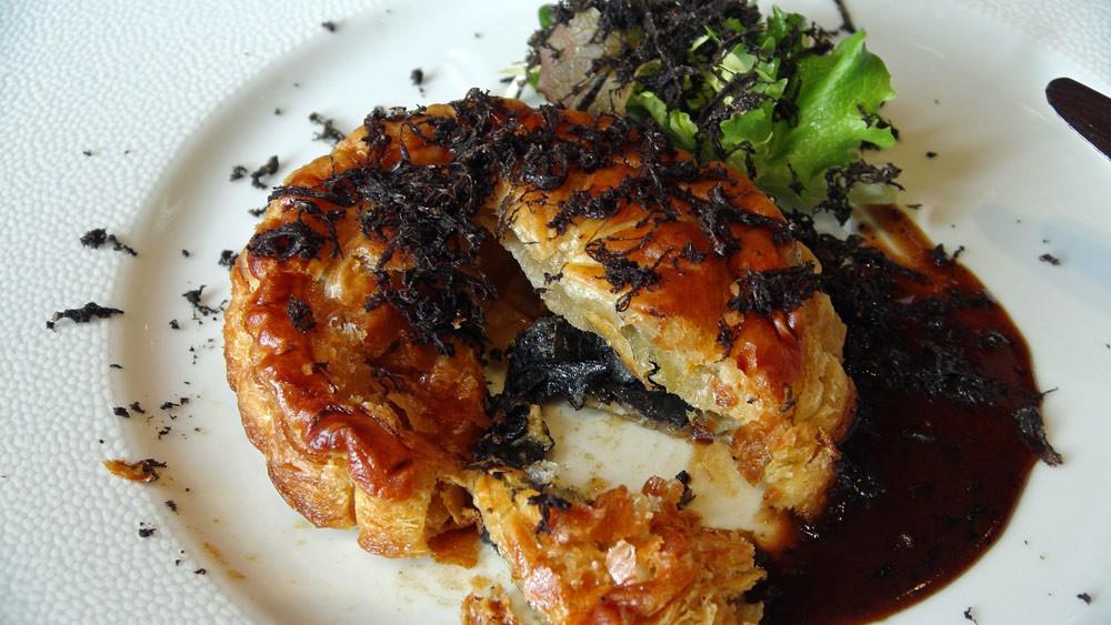 L'intérieur du Pithiviers de foie gras et truffes, sauce Périgueux, quelques pousses d'hiver en vinaigrette, râpée de truffes