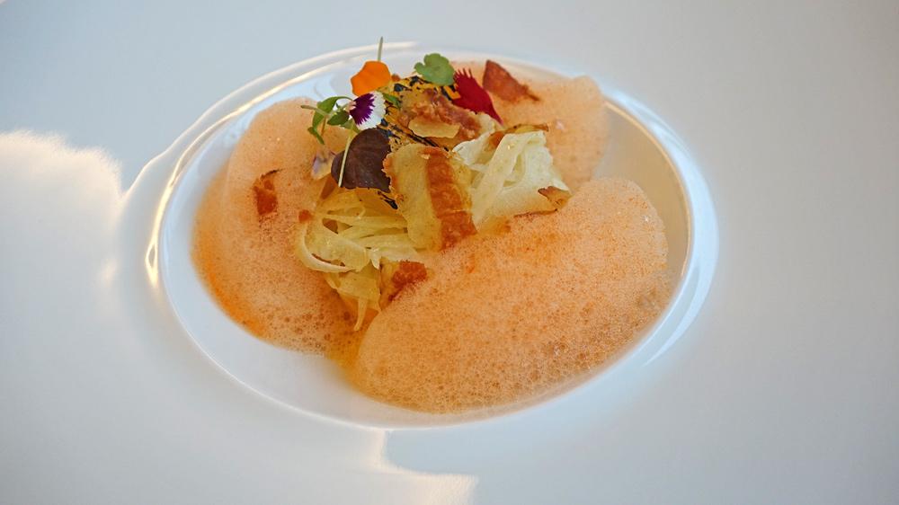 Mousse onctueuse de carotte au carvi noir, fraîcheur de fenouil, émulsion citronnelle, gingembre et lard croustillant