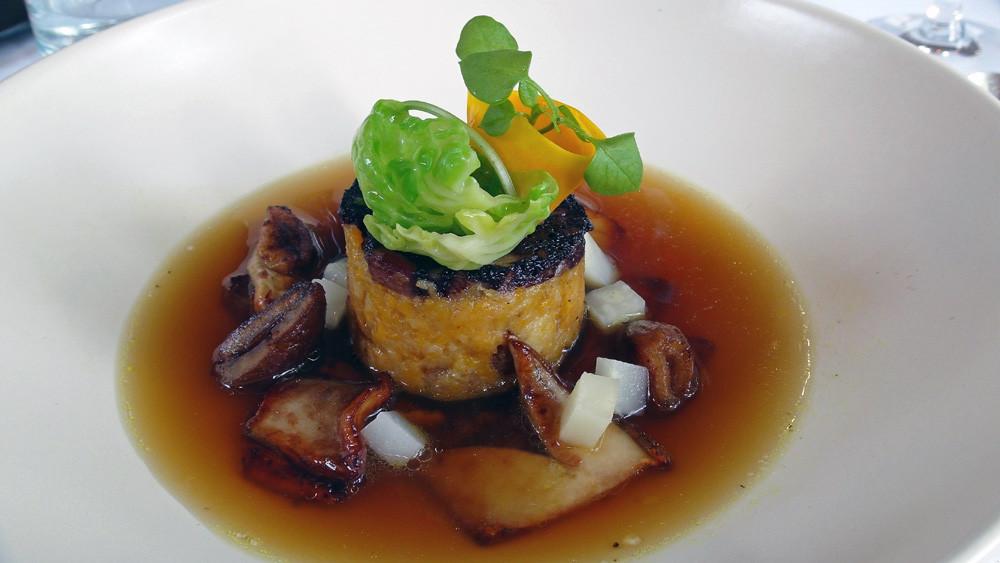 Sur une galette de pain et de potimarron au boudin noir, quelques cèpes, un jus d'oignons caramélisés