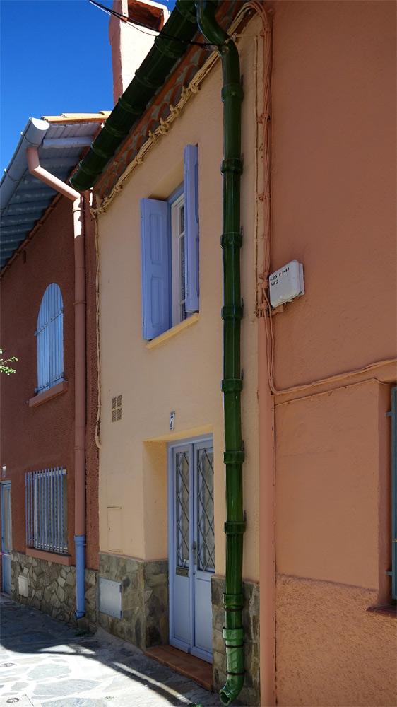 Dans une rue étroite de Collioure, une gouttière en céramique
