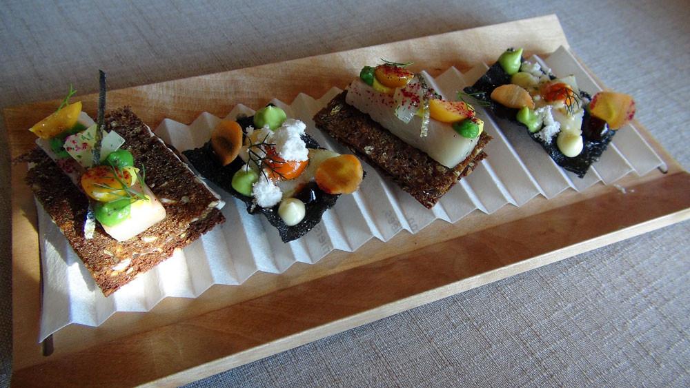 Cracker au Cantal à l'encre de seiche et calamar juste saisi - Pain noir et mélasse, fromage blanc aux herbes, truite fario en gravelax