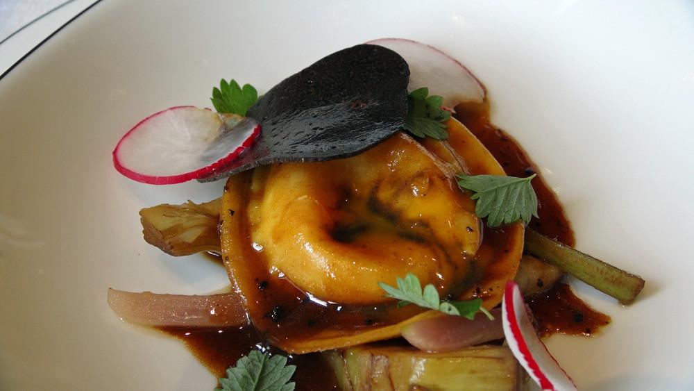 Ravioli garni de jaune d'œuf de ferme confit/cœur coulant truffé, primeurs fondants aux truffes, coupé