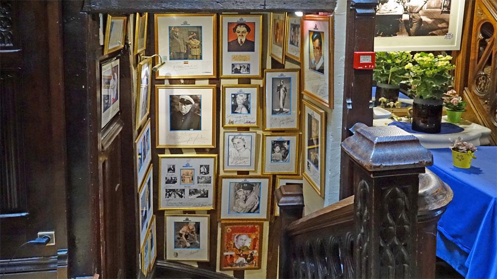 Vue de l'escalier depuis le palier du 1er étage et son décor de photos de personnalités