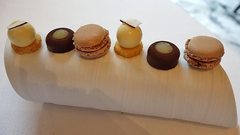 Mignardises : Macaron chocolat/noisette - Ganache chocolat, tonka et poire - Crémeux biscuit/coco.