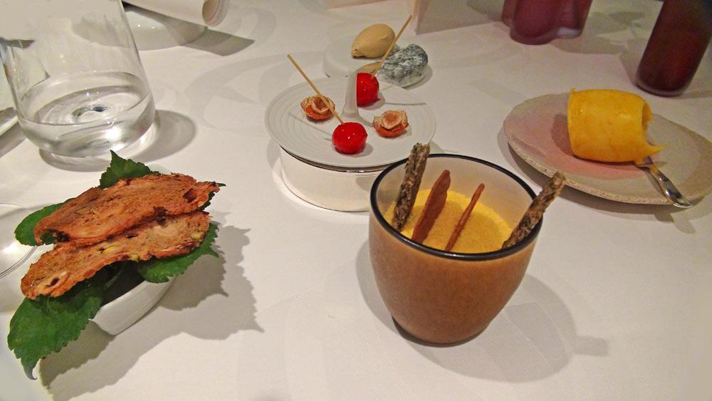 Amuse-bouche : Jus de fraises parfumé à l'eau de vie de sureau, gel de pamplemousse, groseille et mérédi - Dans un dé à coudre, une crème de chou-fleur légèrement truffée - Boule de pain et persil - Gambero rosso crue - Pains divers