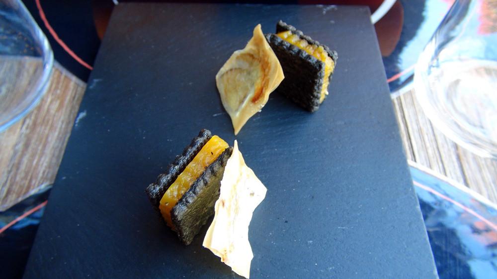Amuse-bouche : Sablé de parmesan à l'encre de seiche, garni de buterrnut confit - Chips et sa lame de cèpe cristallisé