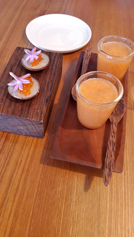 Mise en bouche : Gaspacho de melon et Reine des près séchée (à droite) - Tartelette, crème d'artichaut, fève de Tonka, œufs de truite et fleur d'ail (à gauche)