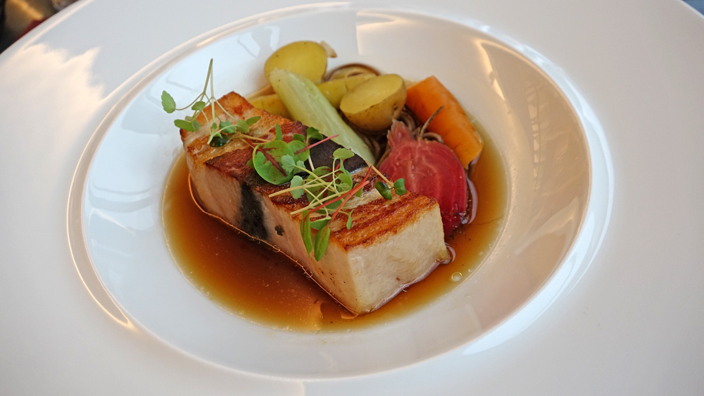 Poitrine de porc fermier d'Auvergne cuite 30 heures au sésame noir et yuzu, bouillon végétal, soba au sarrasin et jeunes légumes