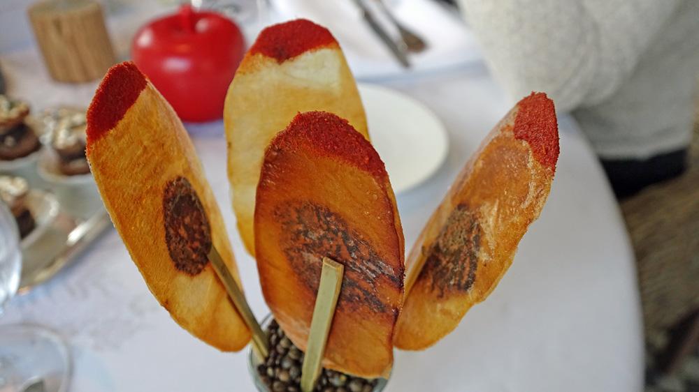 Mise en bouche : Pomme de terre imprimée, olive noire et poudre de tomate