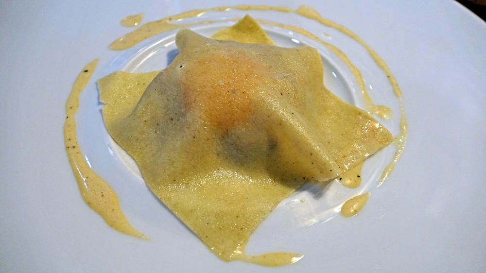 La raviole, jaune d'œuf, noix, ail nouveau et confiture de lait de chèvre