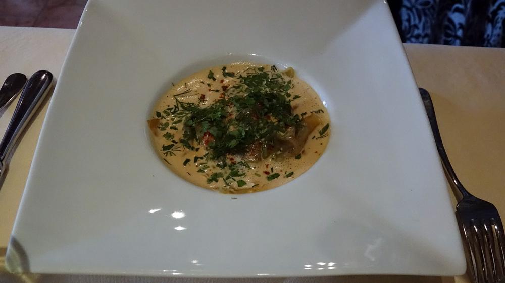 Ravioles de langoustines cuites à la vapeur, servies dans une bisque de homard parfumé au saté