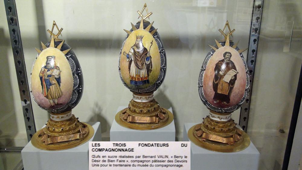 """Les trois œufs en pastillage et colorants alimentaires sont l'œuvre de Bernard Valin, """"Berry le Désir de Bien Faire"""". Réalisés en 1998 pour le trentenaire du musée, ils sont un hommage aux trois fondateurs légendaires du Compagnonnage"""