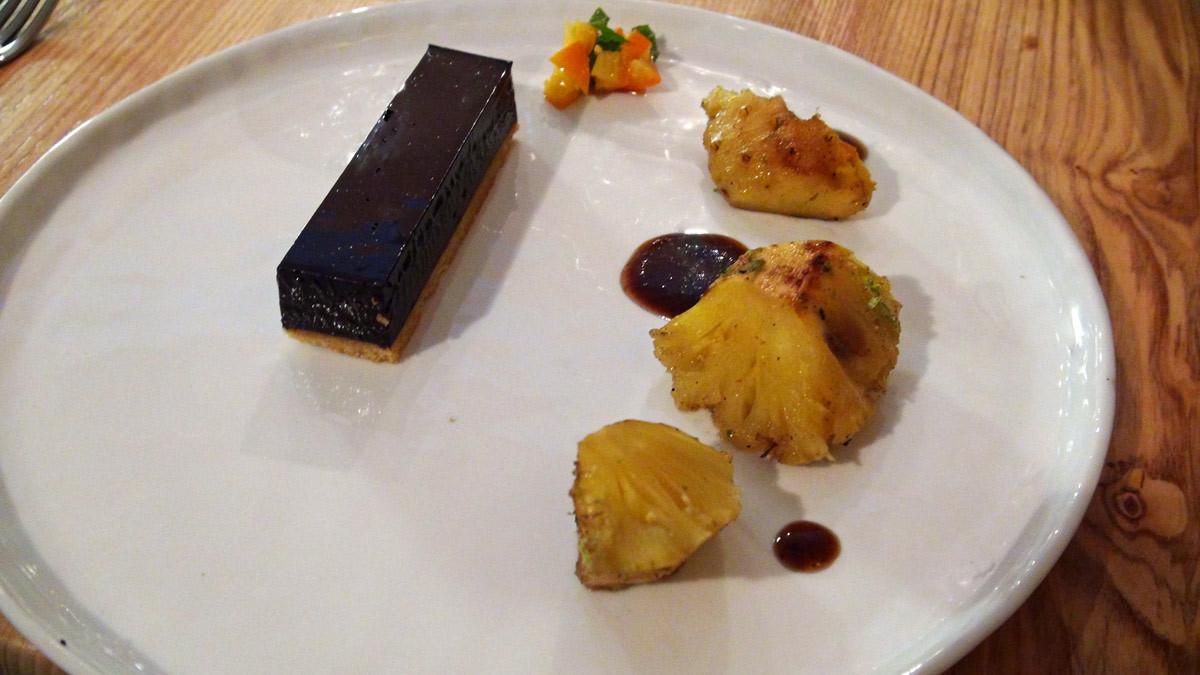 Ananas rôti aux épices, sauce aux pruneaux, tarte chocolat noir/tanaisie, kumquat et feuilles de menthe