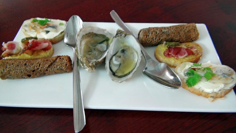 Les amuse-bouche : Huitre de Jersey et huile de basilic,  Galette sarrasin/saucisse, Toast de filet d'anchois mariné et Toast de saucisson du marin, moutarde Savora