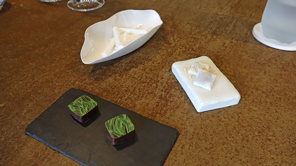Mignardises : Meringue au bonbon arlequin - Mochi au chocolat blanc et poudre d'hibiscus - Chocolat au thé matcha.