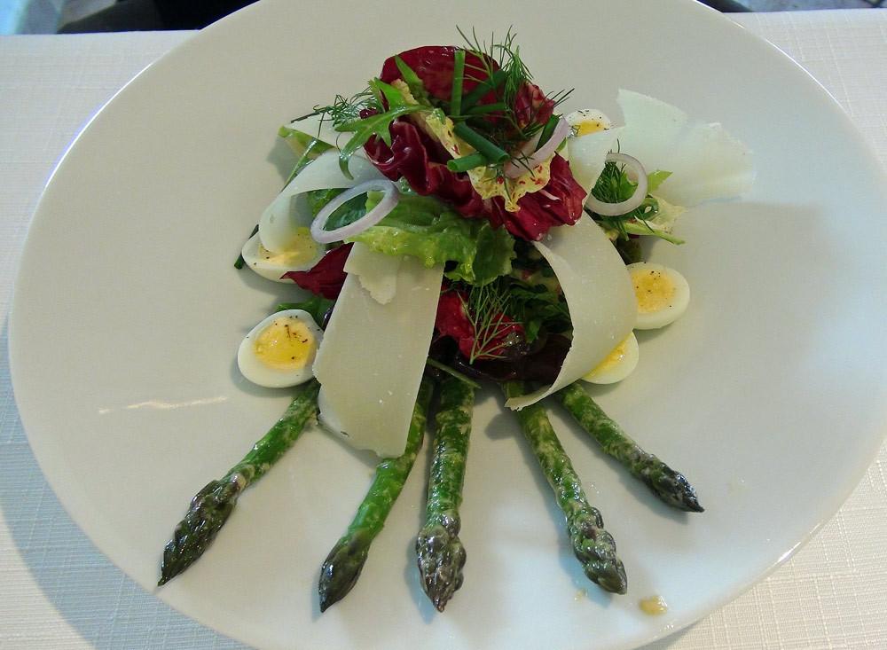 L'asperge servie en mesclun nourri d'herbes aromatiques, du parmesan et des oeufs de caille