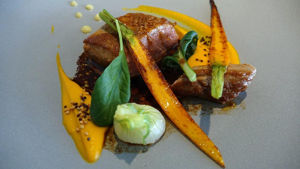 Selle d'agneau, carottes snackées, oignon blanc, jus moutarde à l'ancienne, pomme fruit et curry