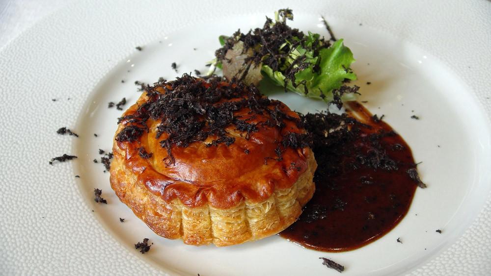 Pithiviers de foie gras et truffe, avec sa sauce Périgueux, quelques pousses d'hiver en vinaigrette, râpée de truffes