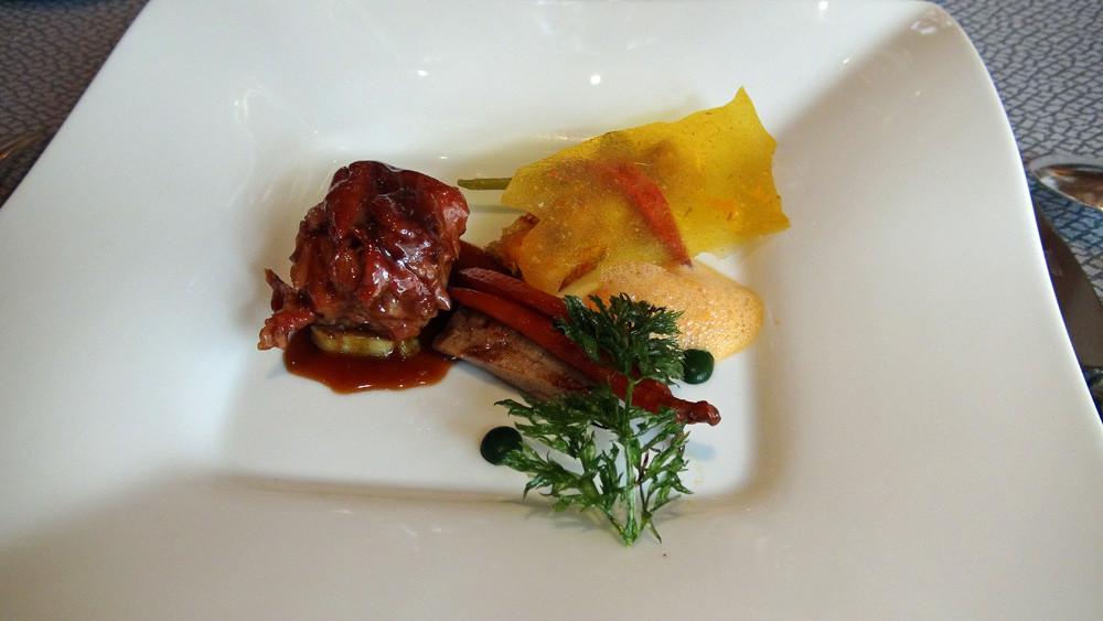 Epaule d'agneau cuite doucement dans ses sucs aux épices, tartine de jeunes carottes et lard de Cul noir au carvi, tuile aromatique