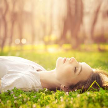 Eine Frau liegt völlig entspannt mit geschlossenen Augen auf dem Rücken im weichen Moos in einer Waldlichtung.