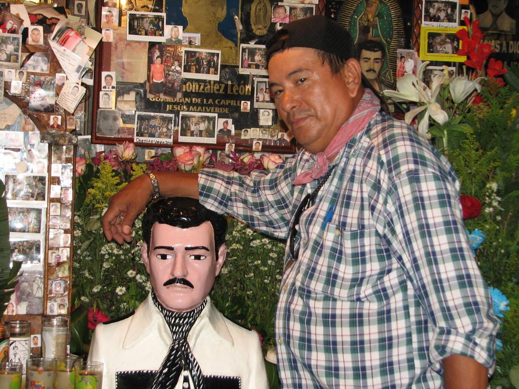 礼拝堂の管理人フランシスコとマルベルデ像。お参りに来た人は像の頭をなで、なぜか自分や家族の写真を壁に貼っていく。