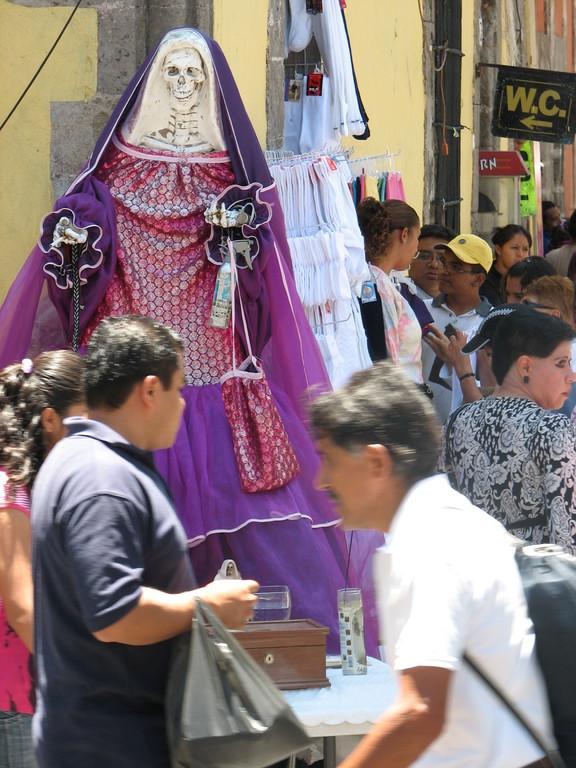 露天商と買い物客でごった返す通りの一角に置かれたサンタ・ムエルテ像