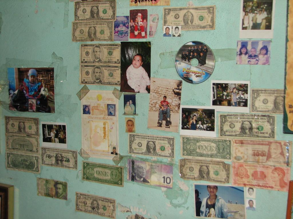 家族の平安を祈って壁に写真を張る。お礼のドル札はしっかり糊づけされています。