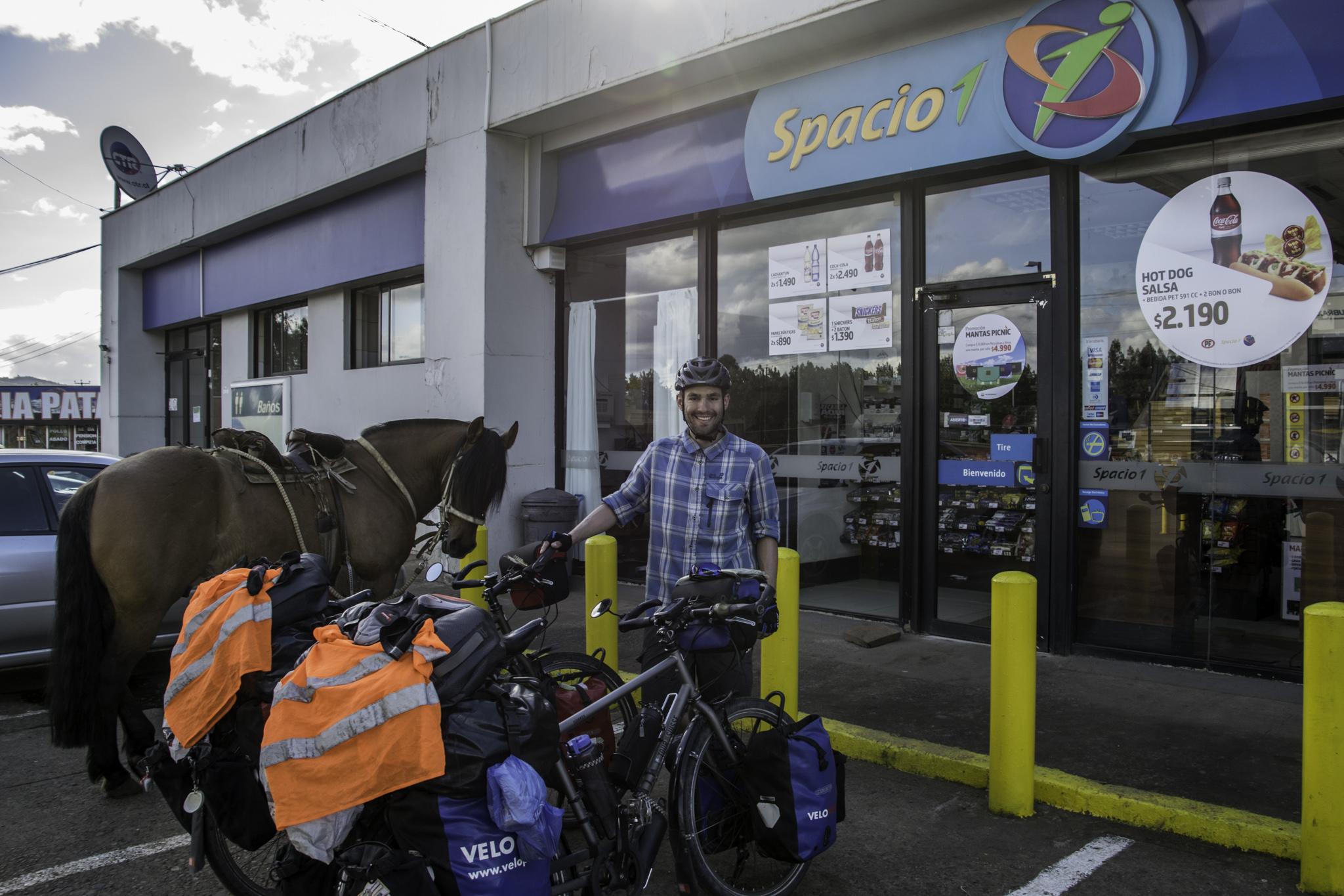 Ein Pferd und zwei kleine Drahteselchen vor einem Tankstellenshop