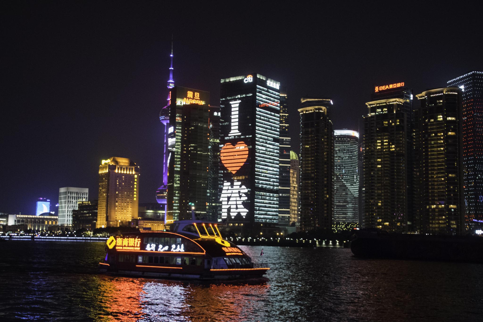 Flussfahrt durch das beleuchtete Shanghai