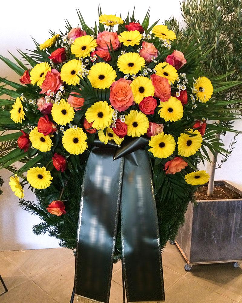 Trauerkranz mit gelben Gerbera, orangen Rosen und mit Kamille gefüllt.
