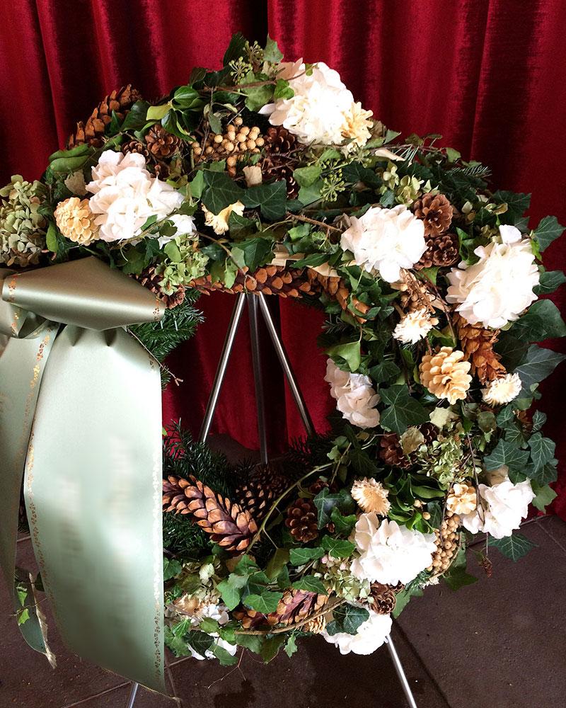 Waldkranz rund mit frischen weißen Hortensien, verschiedenen Zapfen und gemischtem Grün.