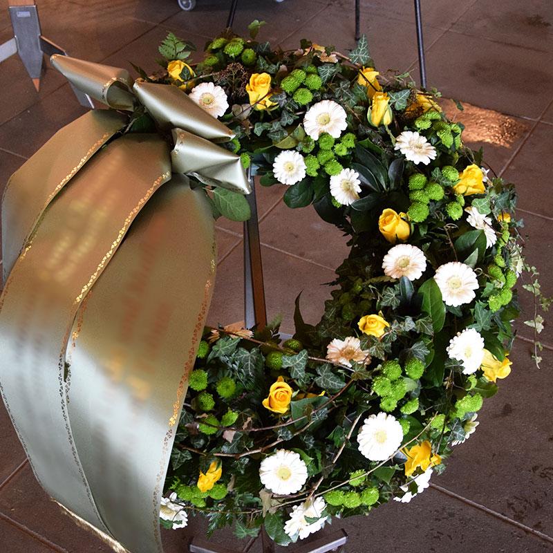 Trauerkranz mit weißen Germini, gelben Rosen, grünen Santini und Efeuranken umspielt.