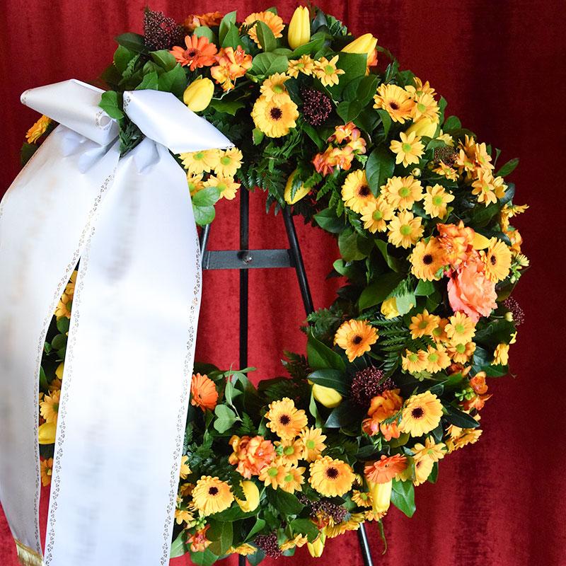 Trauerkranz mit gelben Germini, gelben Tulpen und gelben Chrysanthemen.