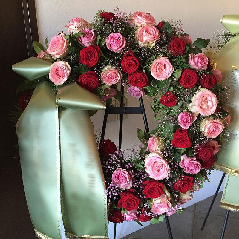 Trauerkranz mit roten und rosa Rosen, gefüllt mit rosa Schleierkraut.