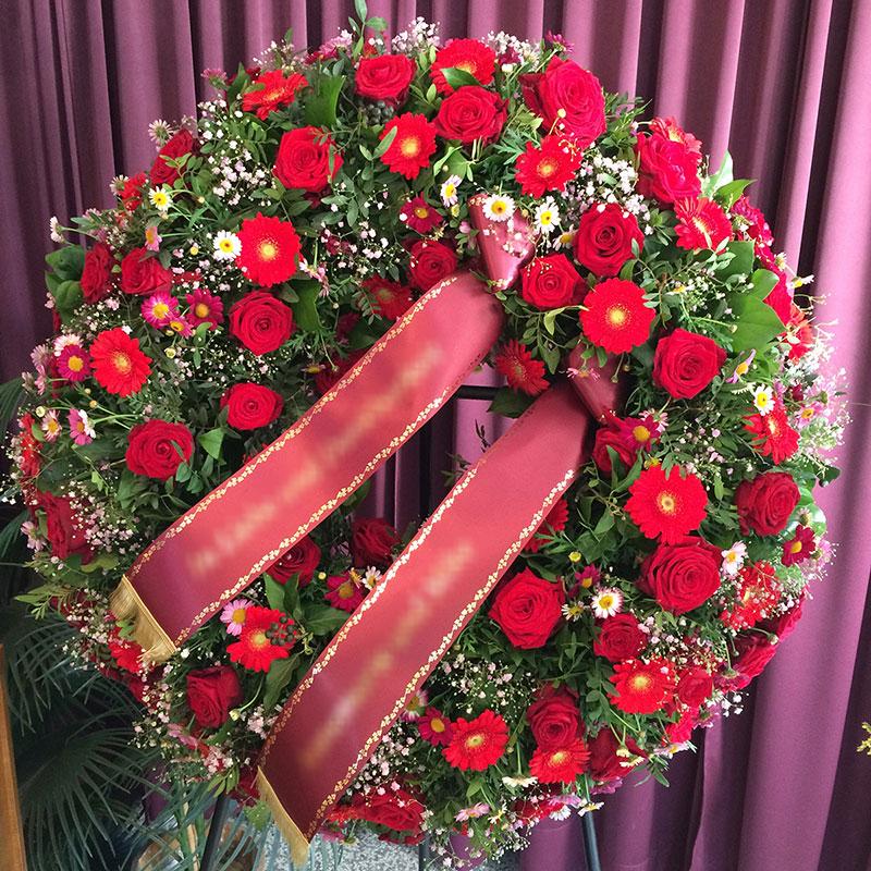 Trauerkranz mit roten Germini, roten Rosen, rosa Margeriten und rosa Schleierkraut.