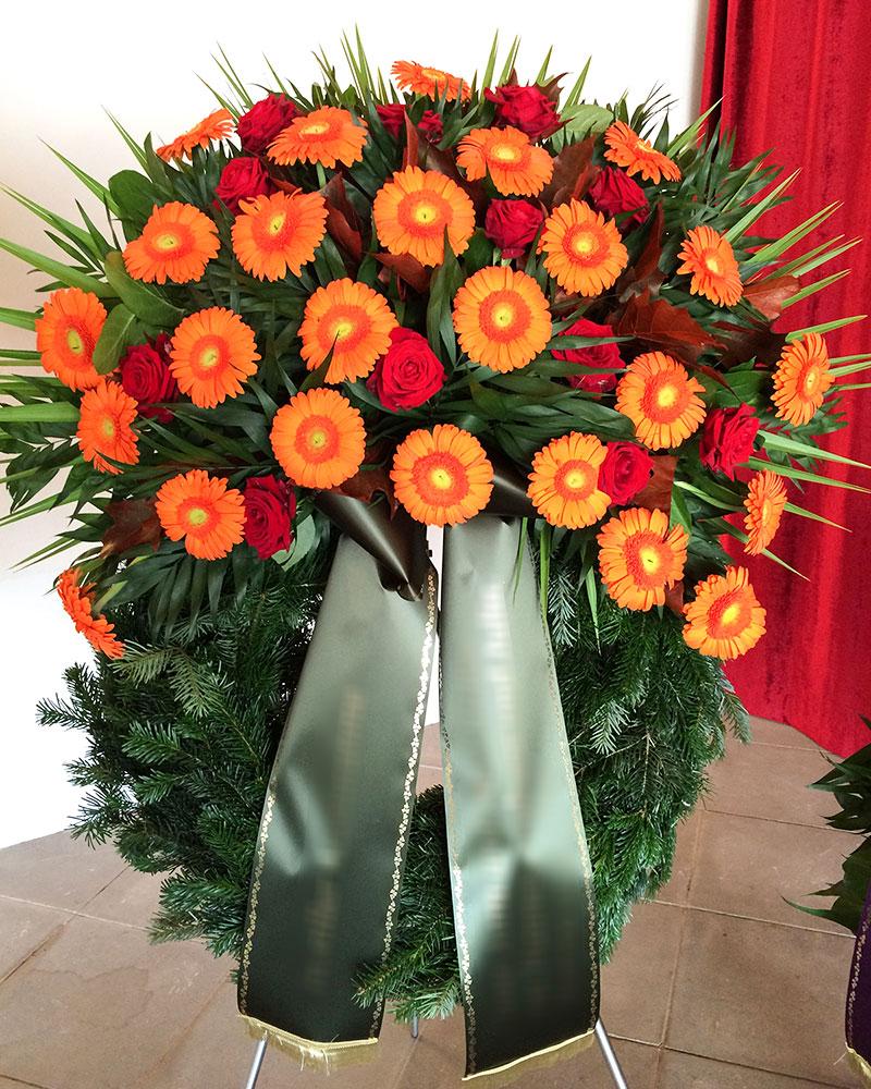 Trauerkranz mit orangen Gerbera, roten Rosen und gemischtem Grün.