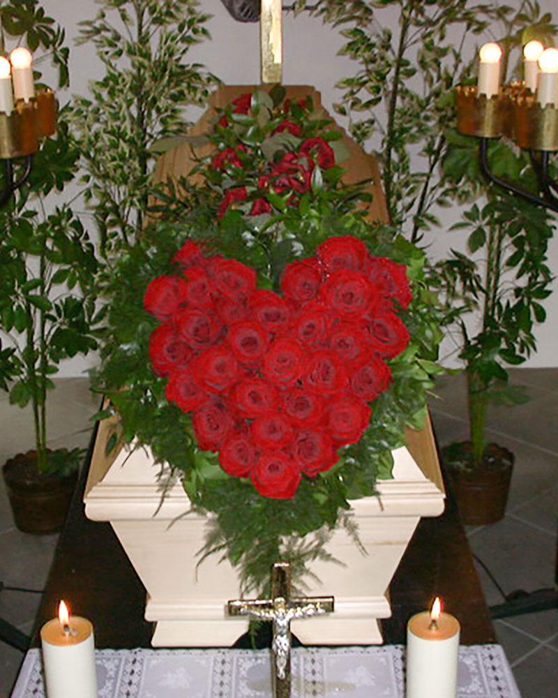 Sargschmuck in Herzform mit roten Rosen.