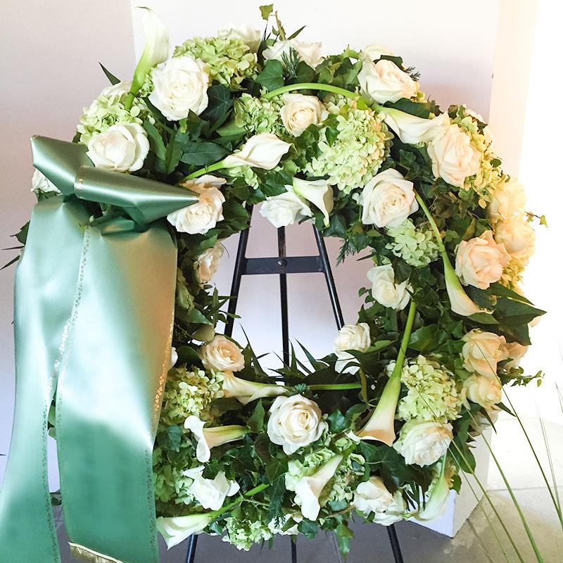 Trauerkranz mit weißen Rosen, weißen Calla und weißen Hortensien.