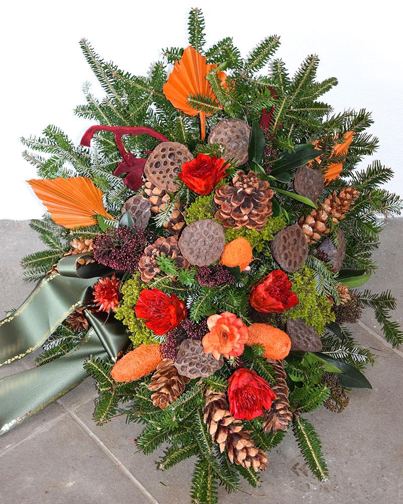 Waldbukett in orange-rot gehalten mit verschiedenen Zapfen und gemischtem Grün.