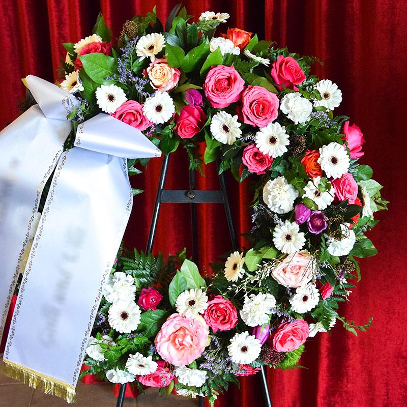 Trauerkranz mit weißen Germini, pinken Rosen, weißen Nelken, lila Tulpen, gefüllt mit lila Limonium.